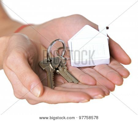Female hands holding keys with house key chain isolated on white