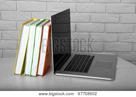 Laptop with books on brick wall background