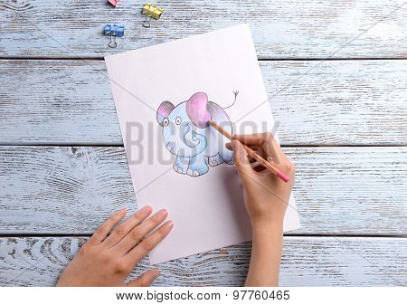 Female hands drawing elephant on sheet of paper on wooden table background