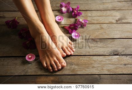 Female feet at spa pedicure procedure with flowers and candlelight on wooden background