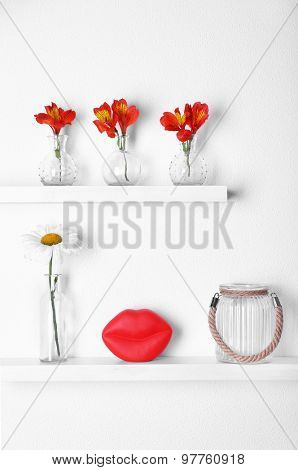Decorative glass vases with flowers  on wooden shelf  on white wallpaper background