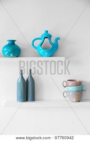 Decorative vases on wooden shelf  on white wallpaper background