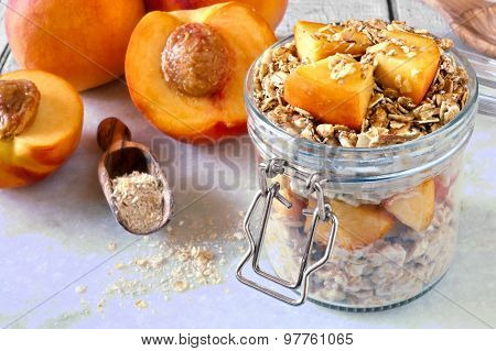 Breakfast oats with peaches and granola in jar on marble