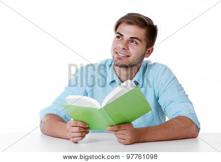 Young man reading book at table on white background