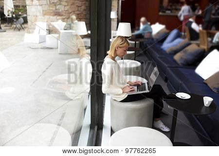 Lovely modern business woman keyboarding on net-book while working in loft studio interior