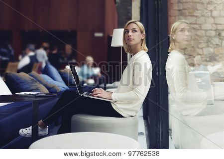 Thoughtful female person sitting in modern coffee shop interior with open laptop computer