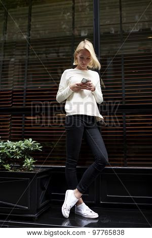 Portrait of trendy hipster girl chat or talk on her mobile phone while standing in the city outdoors