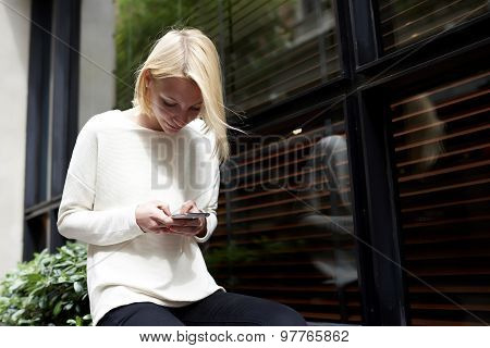 Trendy young woman focused chatting or talk on smartphone near blank copy space background
