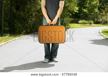 Young man holding vintage suitcase outdoors