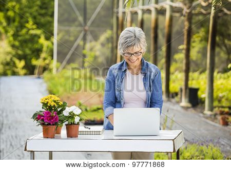 Beautiful mature woman working in a greenhouse holding flowers and taking notes