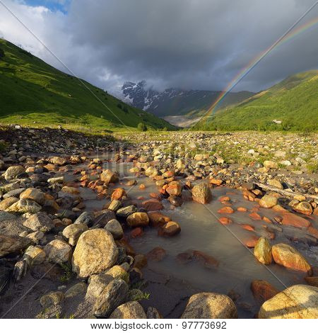 Mountain landscape with river and rainbow. Rainy day. Caucasus, Svaneti, Georgia