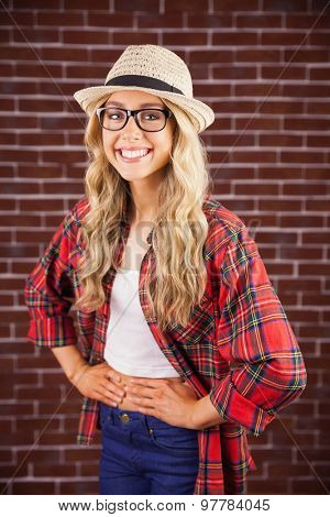 Portrait of gorgeous smiling blonde hipster with hands on hips against red brick background