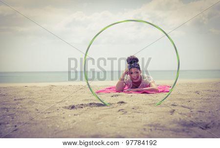 Smiling woman looking at camera through hula hoop at the beach