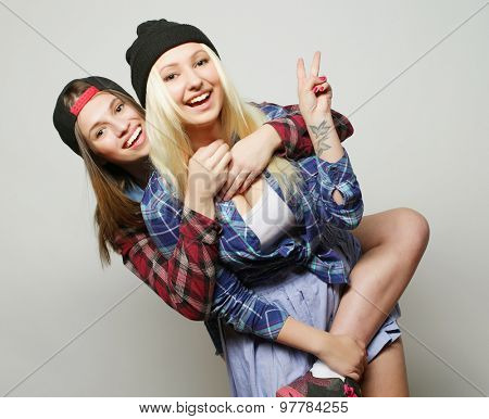 Close up lifestyle portrait of two pretty teen girlfriends smiling and having fun, wearing hipster clothes and hats, positive mood.