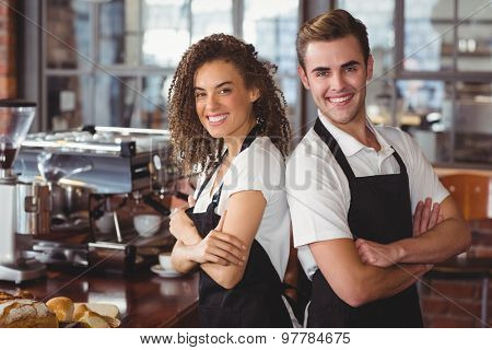 Portrait of smiling colleagues standing back to back at coffee shop