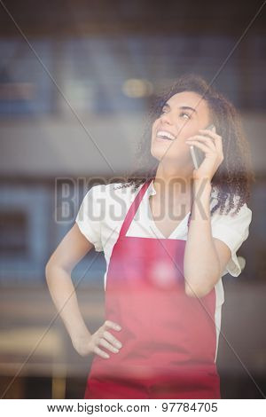 Smiling waitress talking on the phone at the coffee shop