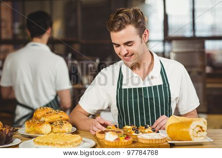 Smiling waiter tidying up the pastries at the coffee shop