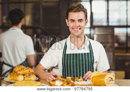 Portrait of a waiter tidying up the pastries at the coffee shop