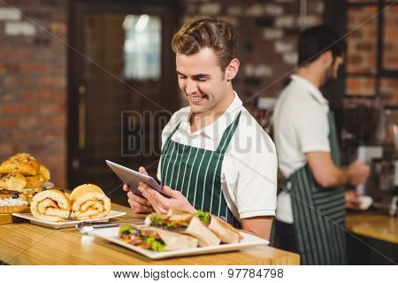 Smiling waiter using a digital tablet at the coffee shop