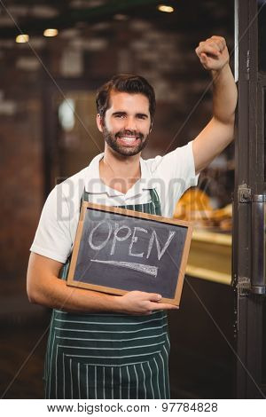 Portrait of a waiter showing chalkboard with open sign at the coffee shop