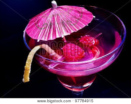 Pomegranate drink with raspberries and umbrella on black background.