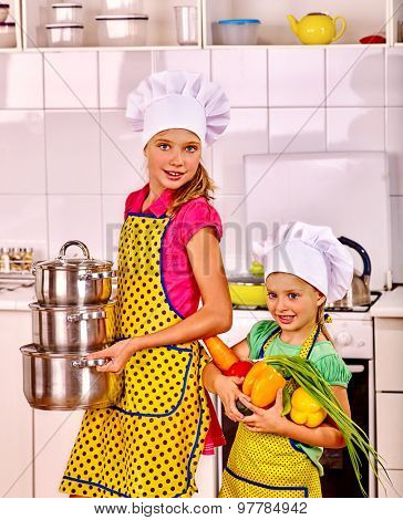 Children wearing hat and apron cooking at kitchen. Little girl grabs vegetables.