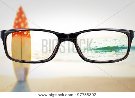 Glasses against surf board standing on the sand