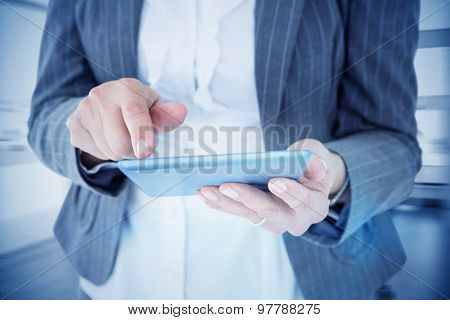 Businesswoman using her tablet against board room