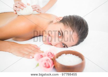 Portrait of a beautiful brunette enjoying a herbal compress massage at the health spa