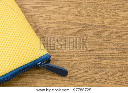 Yellow Bag With Blue Zipper On A Wooden Table