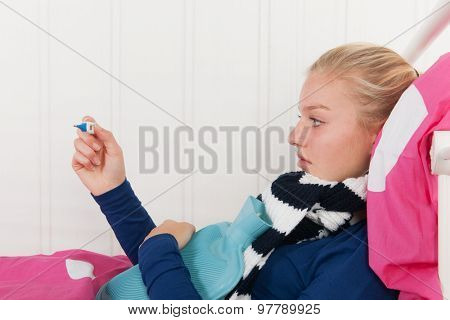 Sick teen girl laying in bed with thermometer for the temperature