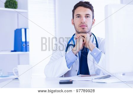 Portrait of doctor looking at camera with hands folded in medical office