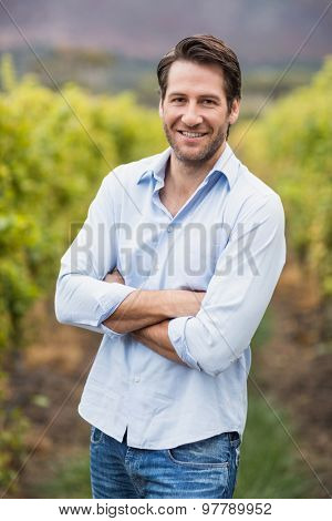 Happy vintner with crossed hands in the fields