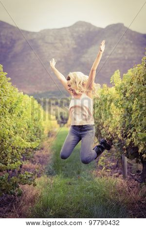 Carefree blonde winegrower jumping in a vineyard