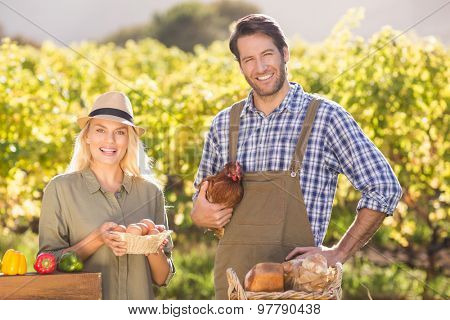 Portrait of a smiling farmer couple holding chicken and eggs