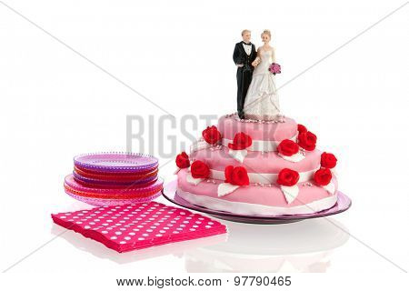 Couple on top of pink wedding cake with red roses isolated over white background