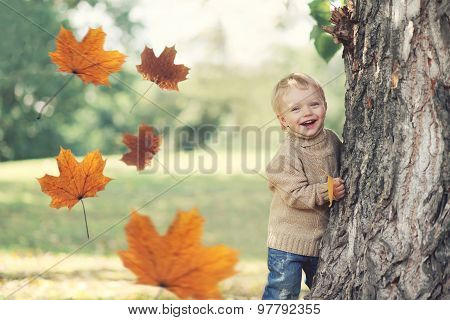 Portrait Of Happy Child Playing Having Fun In Warm Autumn Day With Flying Yellow Maple Leaves