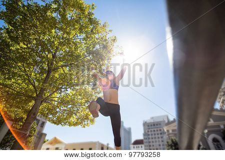 Athletic woman leaping and holding arms up in the air in the city