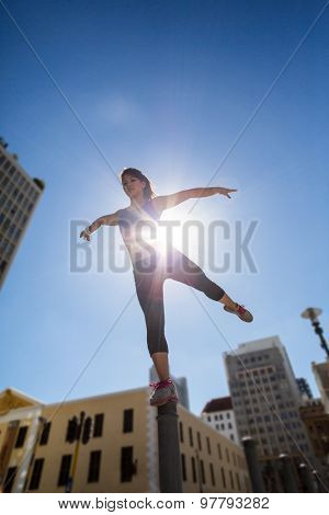 Athletic woman balancing on bollard and stretching out her leg in the city