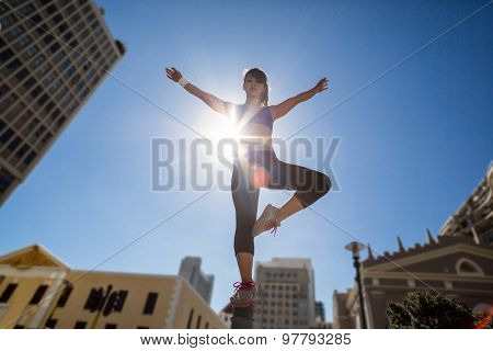 Athletic woman balancing on bollard and stretching out her arms in the city