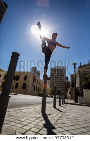 Athletic woman balancing on bollard and holding her leg in the city