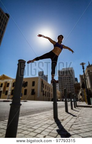 Athletic woman balancing on bollard and stretching out her arms and leg in the city