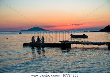 Girls sitting on a pier at sunset in Sithonia