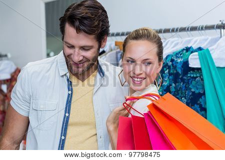 Smiling couple standing next to clothes rail in clothing store