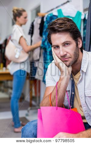Portrait of bored man with shopping bags sitting in front of his girlfriend in clothing store
