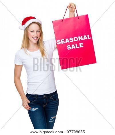 Christmas woman hold with paper bag showing seasonal sale