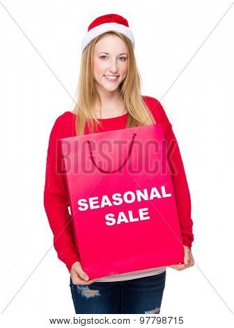 Woman with paper bag showing seasonal sale