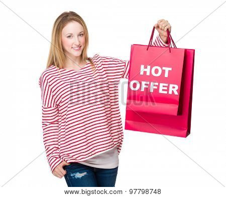 Woman holding with shopping bag and showing hot offer