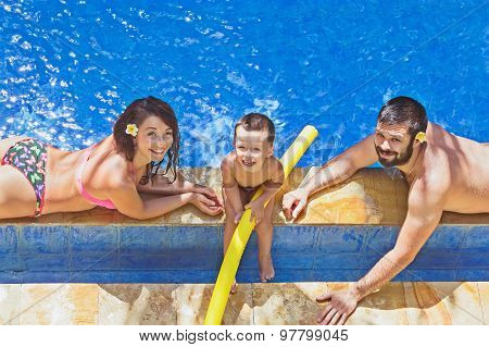 Positive Family Relax In The Outdoor Tropical Pool