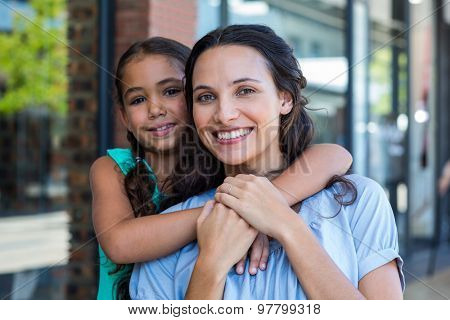 Portrait of a smiling mother and her daughter piggybacking at the mall